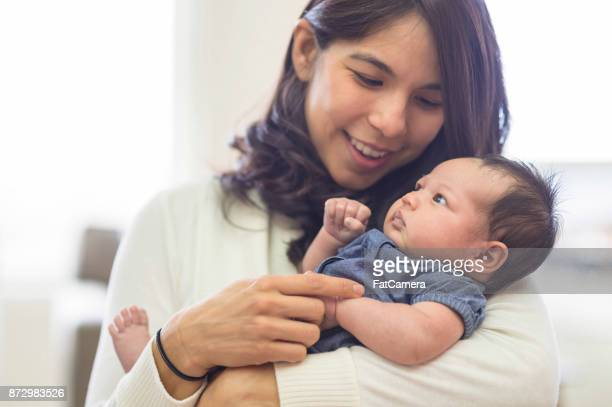 mother cuddling baby daughter at home - latin american and hispanic ethnicity stock pictures, royalty-free photos & images