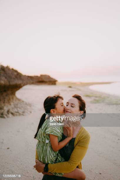 mother cuddling daughter on beach at sunset, japan - ippei naoi stock pictures, royalty-free photos & images