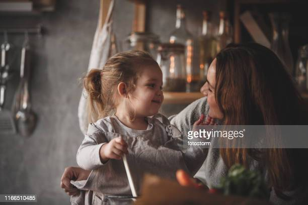 Mother cuddling her two year old daughter while preparing food together