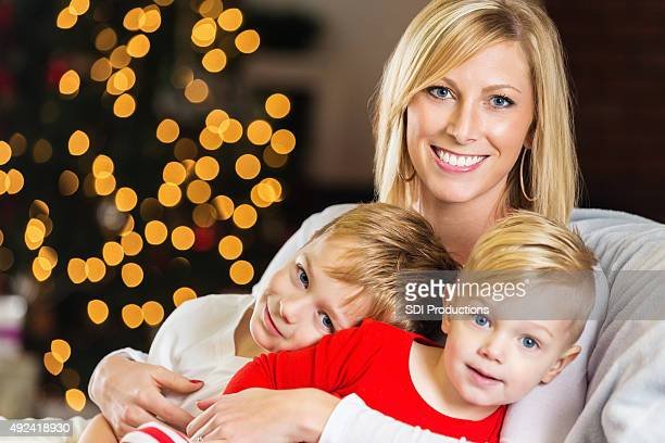 Mother cuddling with young sons on Christmas morning