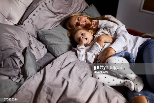 Mother cuddling withdaughter in bed