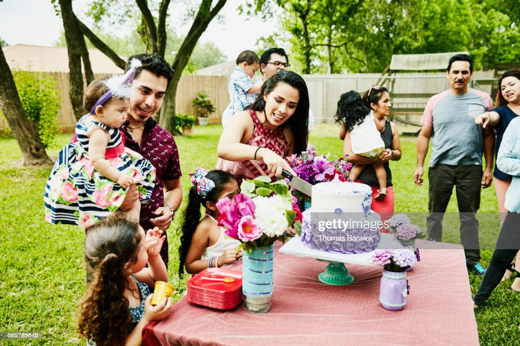 Mother cutting cake for daughter during first birthday party with family in backyard : Stock Photo
