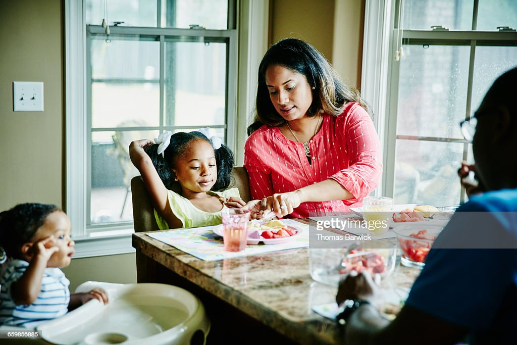 Mother cutting daughters food at breakfast : Stock Photo