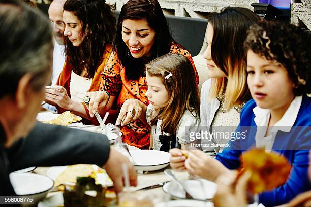 Mother cutting food for daughter during party