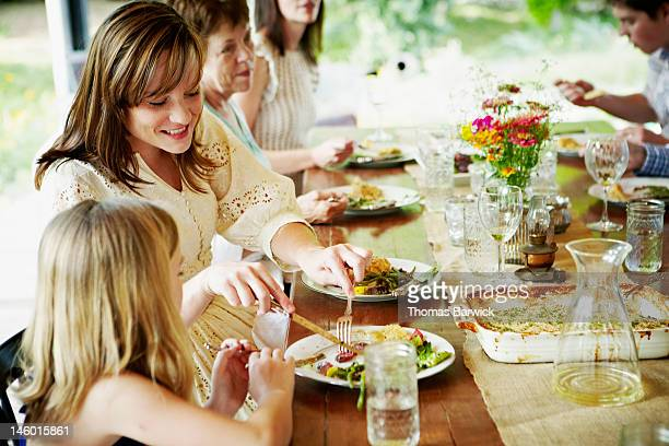 Mother cutting food on daughters plate