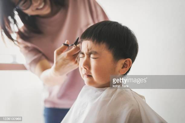 自宅で息子の髪を切る母親 - 髪を切る ストックフォトと画像