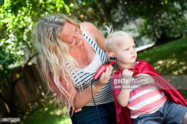 Mother cutting toddler sons hair with clippers