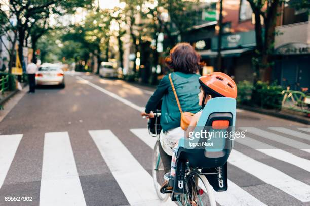 Mother cycling home with her child in urban city, Tokyo