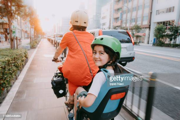 mother cycling home with her preschool child at sunset in tokyo - family with one child stock pictures, royalty-free photos & images