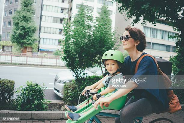 Mother cycling with her child in city, Tokyo
