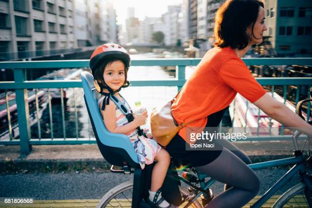 Mother cycling with her child in urban city, Tokyo