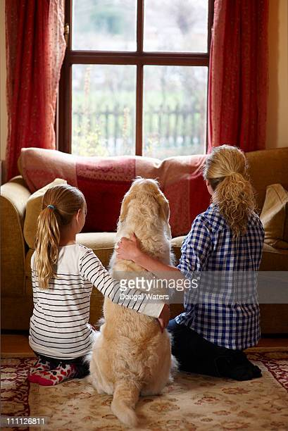Mother, daughter and dog looking out of window.