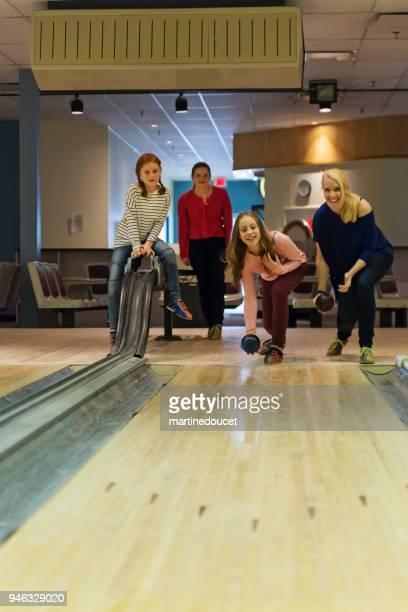 Mutter, Tochter und Freunden Bowling spielen.