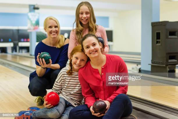 Mother, daughter and friends posing in bowling alley.