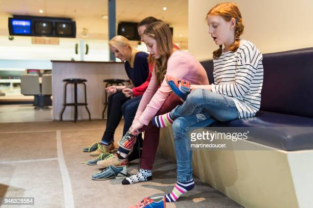 mother, daughter and friends putting on bowling shoes. - girls in socks stock photos and pictures