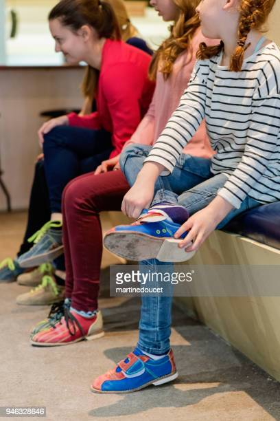 Mother, daughter and friends putting on bowling shoes.