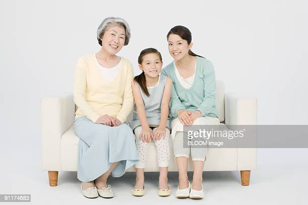 Mother, daughter and granddaughter sitting on couch