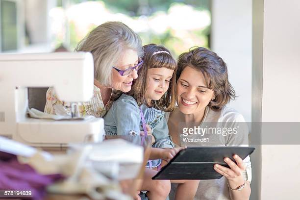Mother, daughter and grandmother working on sewing machine