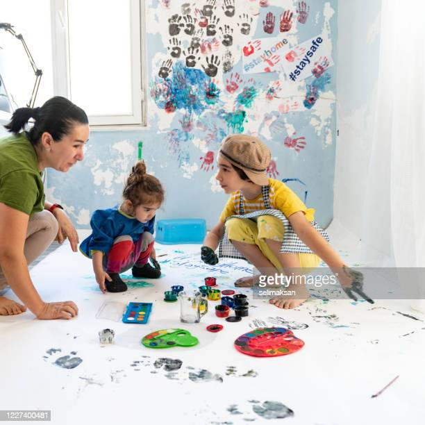 mother, daughter and son finger painting at home - finger painting stock pictures, royalty-free photos & images