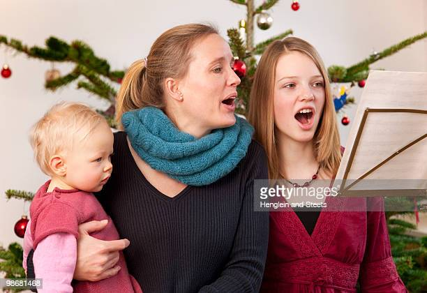 mother, daughter, baby singing carols