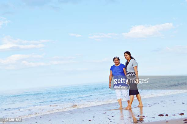 mother daughter duo taking a walk at a beach on a bright sunny summer day - close to stock pictures, royalty-free photos & images