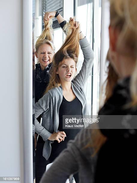 Mother & daughter having fun in front of mirror