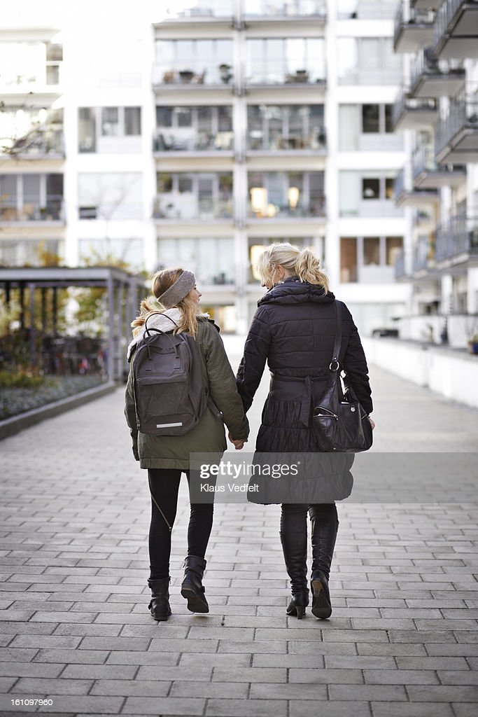 Mother & daughter holding hand while walking : Stock Photo