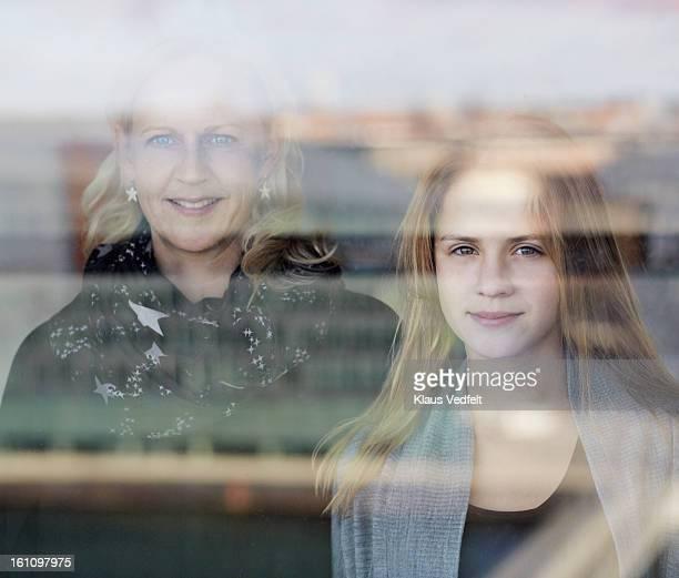 Mother & daughter looking threw big window