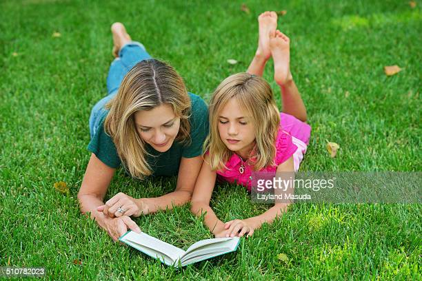 mother daughter outdoor reading - barefoot feet up lying down girl stock photos and pictures