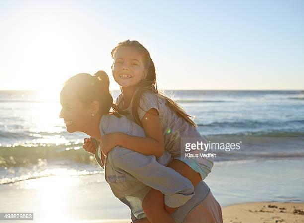Mother & daughter piggybacking on beach