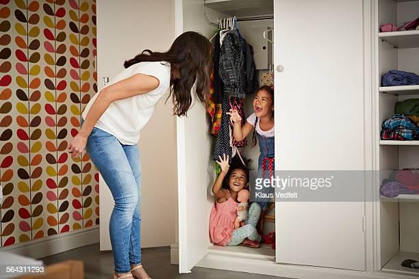 mother & daughter playing hide & seek in closet - esconder imagens e fotografias de stock