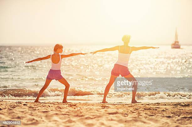 Mother daughter practicing joga on beach
