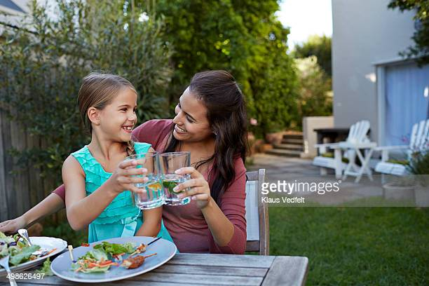 mother & daughter toasting in water with lime
