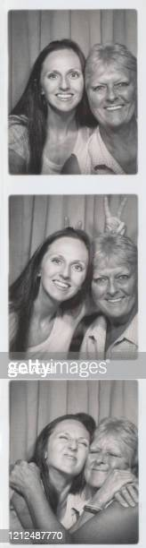 mother daughter togetherness, photo booth photograph nostalgia - black and white instant print stock pictures, royalty-free photos & images