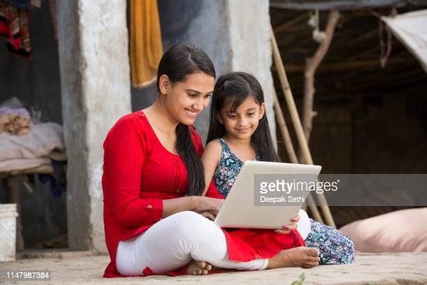 mother daughter using laptop - stock images - village stock pictures, royalty-free photos & images