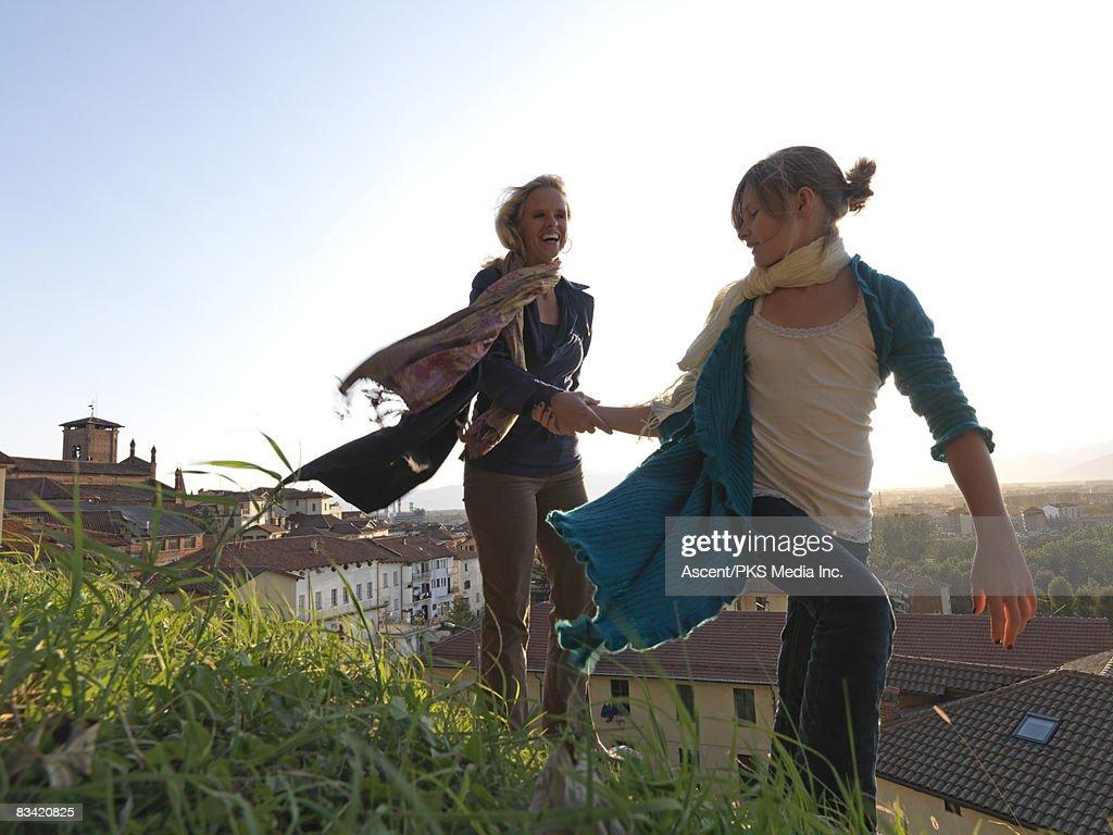 Mother & daughter walk in wind above town : Bildbanksbilder