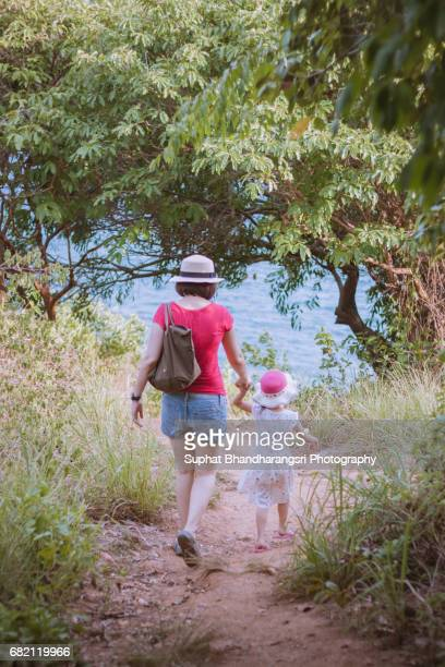 Mother & daughter walking down the hill to the sea
