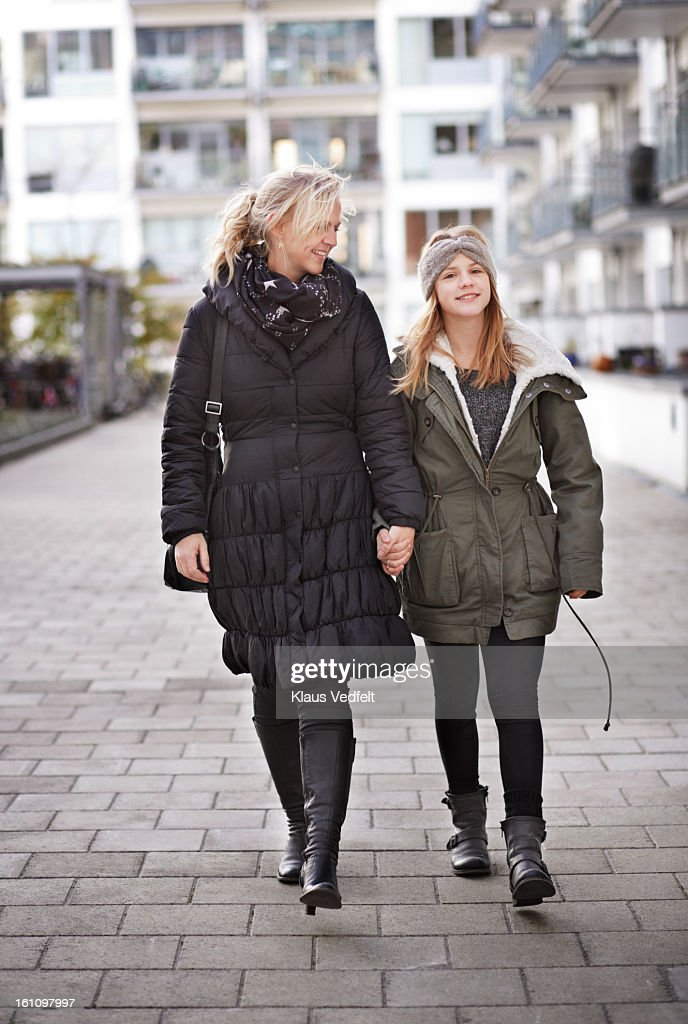 Mother & daughter walking & holding hands : Stock Photo