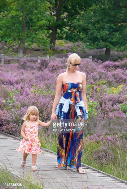 mother & daughter walking on boardwalk - long dress stock pictures, royalty-free photos & images