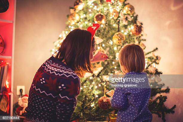 mother decorating christmas tree with her son - abeto fotografías e imágenes de stock