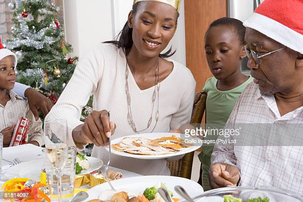 Mother dishing up Christmas lunch with her family around her at Christmas.