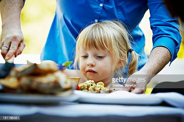 Mother dishing up food for toddler at table