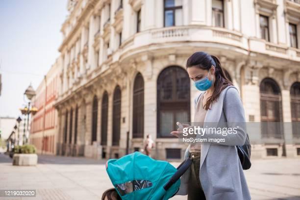 la mère désinfecte ses mains dans la rue - serbie photos et images de collection