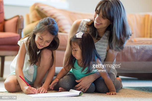 Mother doing arts and crafts with her young daughters
