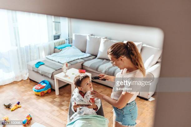mother doing haircut to her son during total lock down - total look stock pictures, royalty-free photos & images