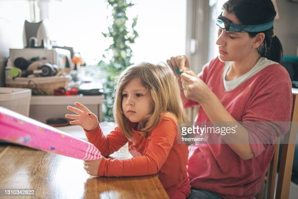 mother doing head lice inspection on daughter - louse stock pictures, royalty-free photos & images