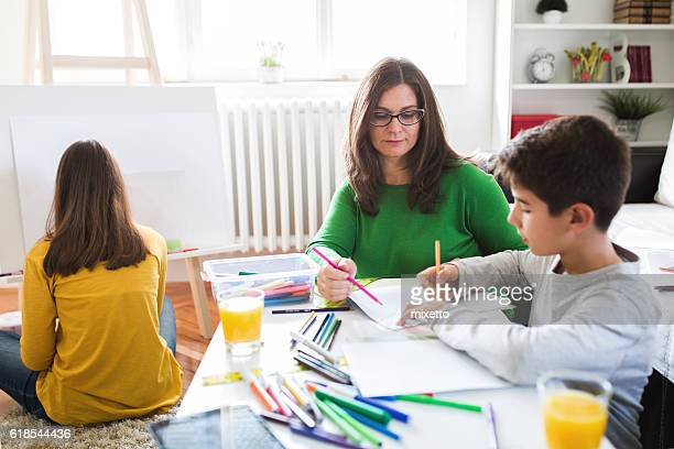 Mother Doing Homework With Their Children