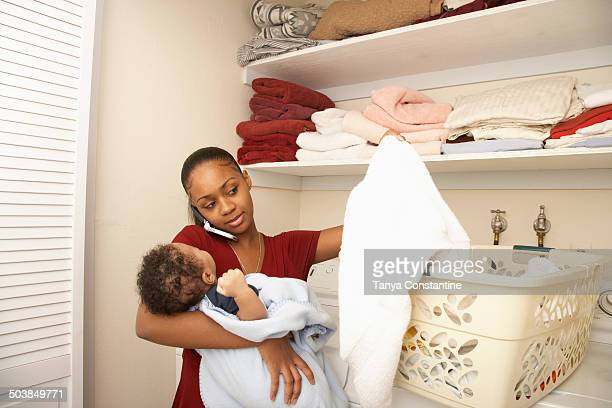 Mother doing laundry, holding baby and talking on cell phone