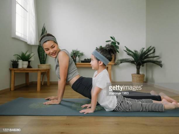 mãe fazendo em tapete de ioga com a filhinha em casa. - praticar - fotografias e filmes do acervo