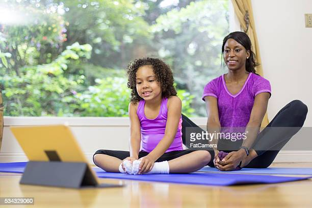 Mother doing yoga fitness at home with her young daughter